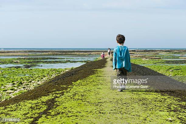 Boy walking on breakwater, Ile de RŽ, Charente-Maritime, France