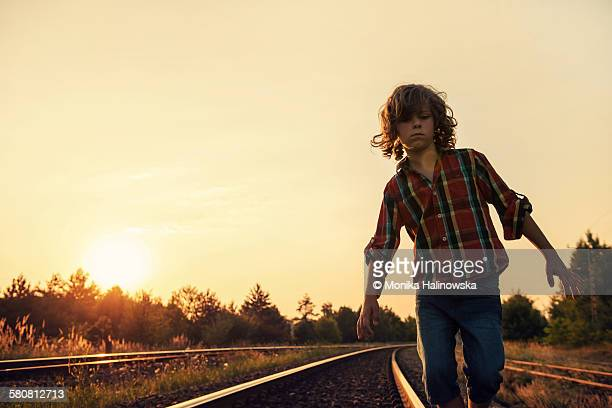 Boy walking on railway track