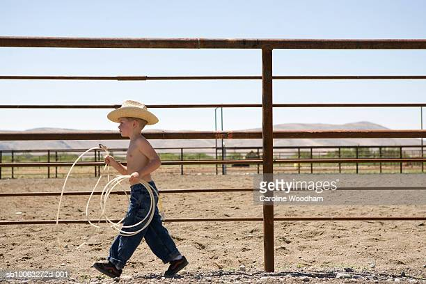 Boy (6-7) walking on ranch, carrying lasso, profile