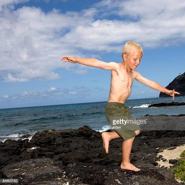 Boy (8-9) walking on rock at beach