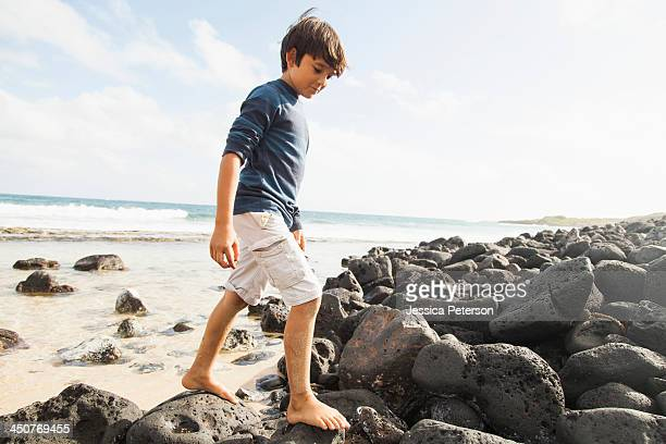 Boy (10-11) walking on stones on beach