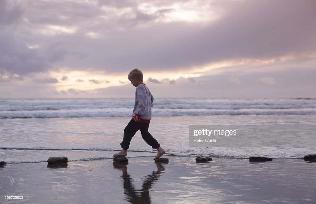 Boy walking over stepping stones sea : Stock Photo