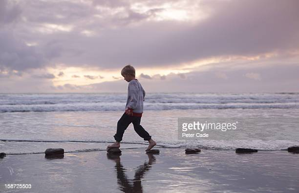 Boy walking over stepping stones sea