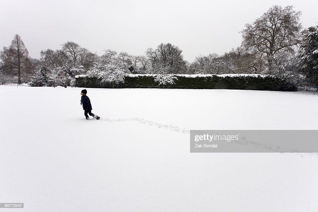 Boy walking through snow field