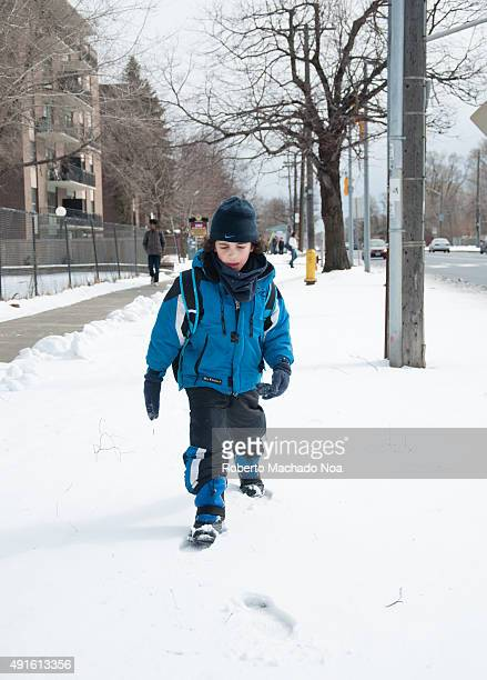 Boy walking through snow He is wearing a thick blue jacket black pants black gloves and a black hat Several bare trees telephone poles a building a...