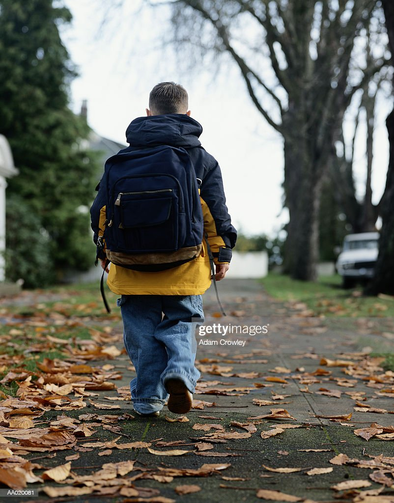 Boy Walking to School Carrying a Backpack