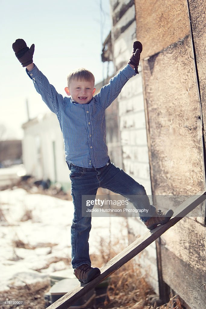 Boy walking up plank : Stock Photo
