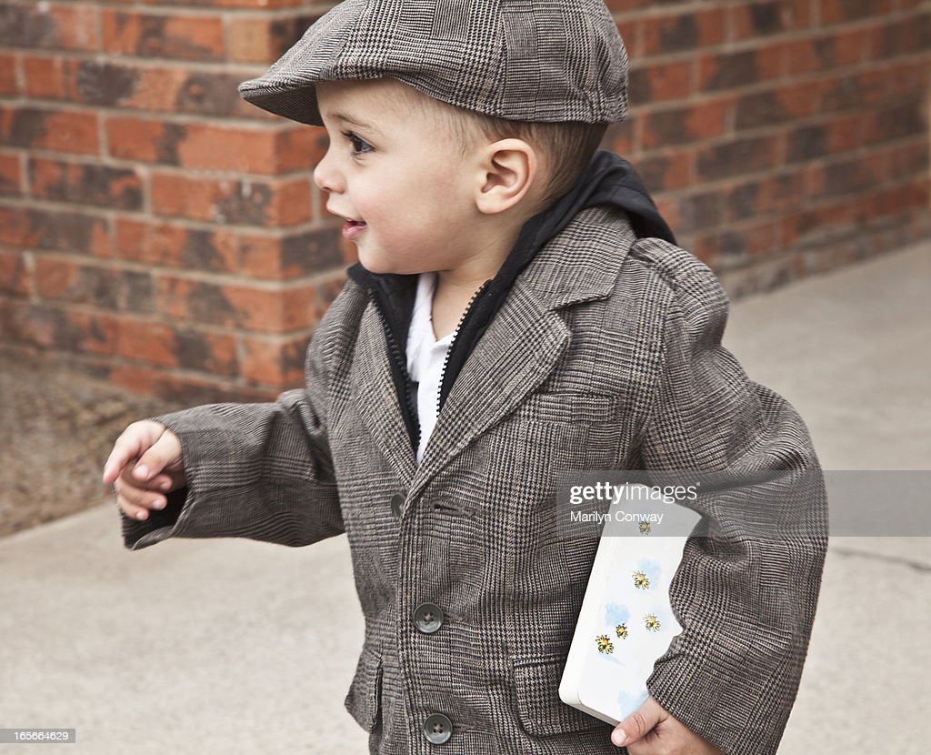 Boy walking with book : Stock Photo