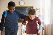 Boy walking with friend on crutches