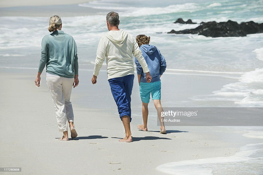 Boy walking with his grandparents on the beach : Stock Photo