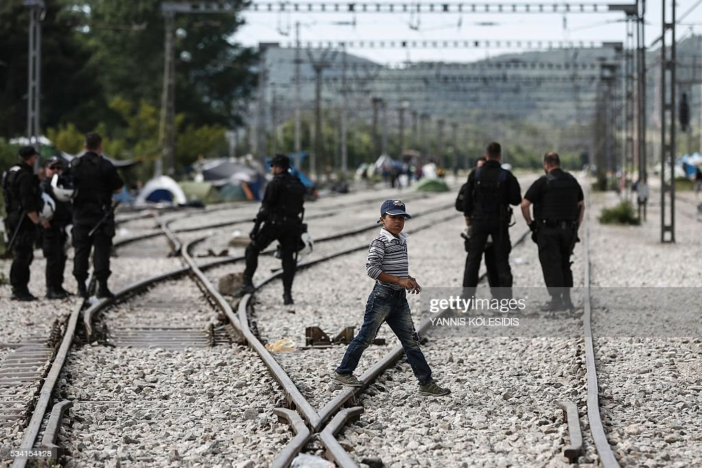 A boy walks acros rail tracks during a police operation to clear a makeshift camp for refugees and migrants at the border between Greece and Macedonia near the village of Idomeni, northern Greece on May 25, 2016. Greek police restarted an operation to move migrants out of Idomeni, the squalid tent city where thousands fleeing war and poverty have lived for months. The migrants and refugees on May 24 were bussed to newly opened camps near Greece's second city Thessaloniki, about 80 kilometres (50 miles) to the south. / AFP / POOL / YANNIS