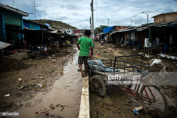 TOPSHOT A boy walks along a low wall on a muddy road after the flooding caused by recent rains in the province of Paita in Piura northern Peru on...