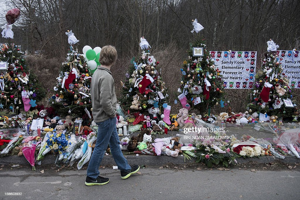 A boy walks along a makeshift memorial near Sandy Hook Elementary School on December 20, 2012 in Newtown, Connecticut. People continue to mourn the killing of 20 students and 6 adults by alleged gunman Adam Lanza at Sandy Hook Elementary School last December 14. AFP PHOTO/Brendan SMIALOWSKI