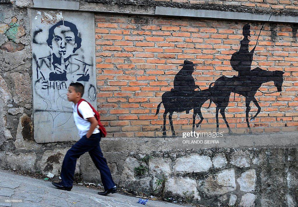 A boy walks along a street in the poor community of Las Ayestas, in Tegucigalpa on February 5, 2013. Honduras' notorious street gangs, especially the Mara 18 and the Mara 13 or Salvatrucha, have imposed a curfew and are charging a 'war tax' in some of the capital's poorest sectors -- thing which led the police to deploy more personnel in theses areas. The violent maras are active in murders, extorsion, drug dealing, arms trafficking and other crimes. The United Nations says Honduras, a country plagued by powerful street gangs and drug-related violence, has the world's highest homicide rate. In 2010 it was 82 per 100,000 inhabitants, and rose to 86 in 2011. By comparison, in drug-cartel-plagued Mexico, for instance, the rate was about 18 in 2010. AFP PHOTO/Orlando SIERRA