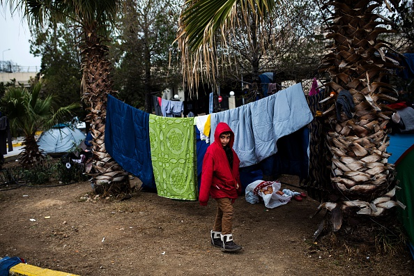 A boy walks among tents outside a passenger terminal used as shelter for refugees and migrants at the Piraeus harbour in Athens on March 12, 2016. Greece aims to deal swiftly with the migrant overf...