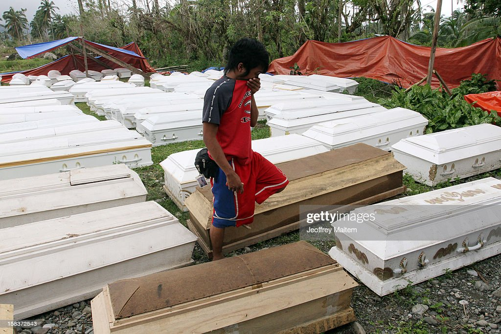 A boy walks among the coffins of the dead in a heavily devastated town December 14, 2012 in New Bataan, Compostela Valley province, Philippines. More than 900 people have been killed and nearly a thousand others remain missing after Typhoon Bopha, the strongest storm to hit the Philippines this year, pounded the region.