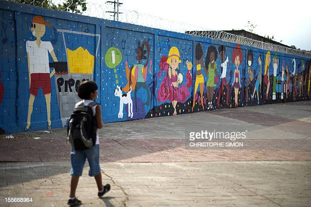 A boy walks by a graffiti on the wall of Maracana subway station in Rio de Janeiro on November 6 2012 Metro Rio asked grafitti artists to paint Rio's...