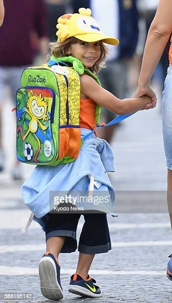 A boy walks down a street in Rio de Janeiro with a hat and bag bearing the image of Vinicius the official Rio Olympic mascot on July 28 2016 He says...