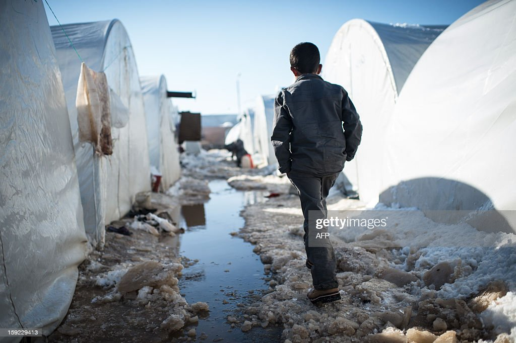 A boy walks in a pathway covered with snow in a Syrian refugees camp in Azaz, near the Turkish border, on January 10, 2013 after snow falls. Snow carpeted Syria's war-torn cities but sparked no let-up in the fighting, instead heaping fresh misery on a civilian population already enduring a chronic shortage of heating fuel and daily power cuts. AFP PHOTO / EDOUARD ELIAS