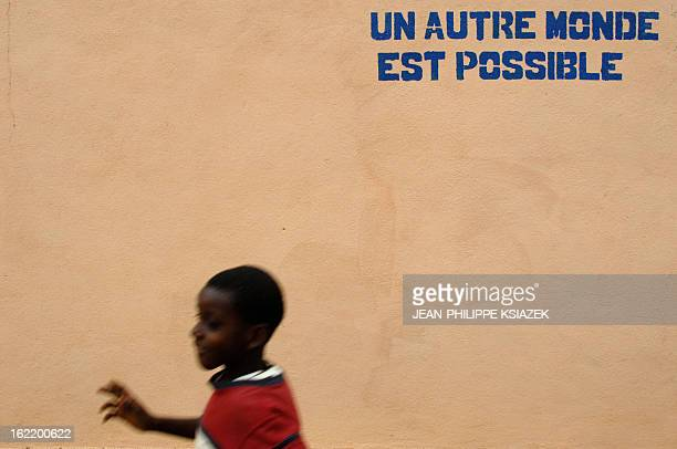 A boy walks in a street near a wall where 'Another world is possible' had been painted on the opening day of the 6th World Social Forum 19 January...
