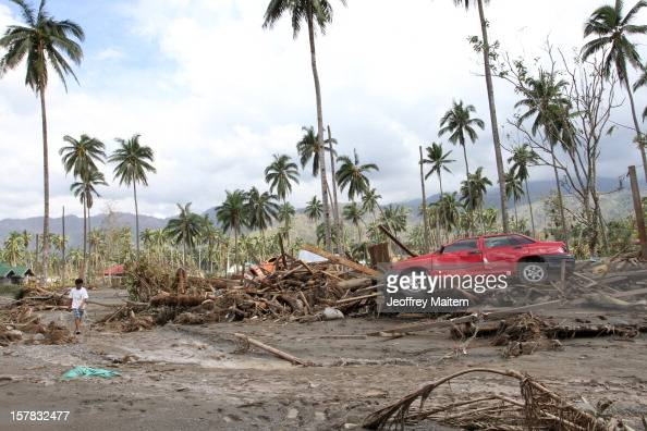 A boy walks in floodhit village brought about by typhoon Bopha in the southern Philippine township of New Bataan Philippines More than 500 people...