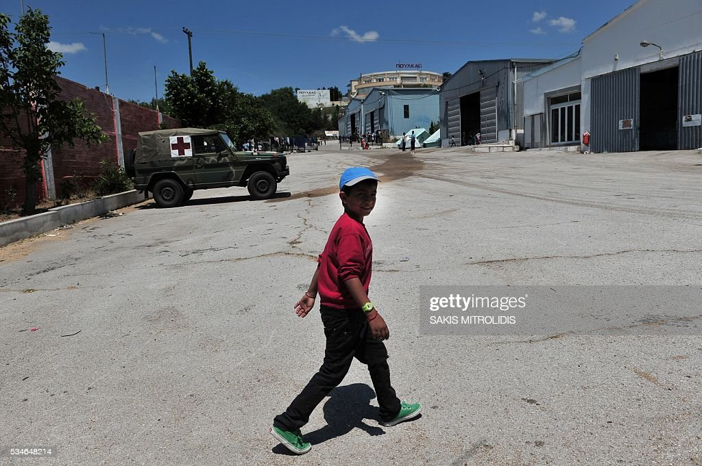 A boy walks inside a new camp for refugees and migrants set in an abandoned factory in Sindos, a west suburb of Thessaloniki on 27 May, 2016. The squalid Idomeni refugee camp in northern Greece which became a symbol of Europe's migrant crisis has been fully evacuated, police said Thursday, as another 30 died crossing the Mediterranean. In the space of three days, police transferred about 4,000 migrants by bus from Idomeni to newly created camps in the industrial outskirts of Greece's second city Thessaloniki. / AFP / SAKIS