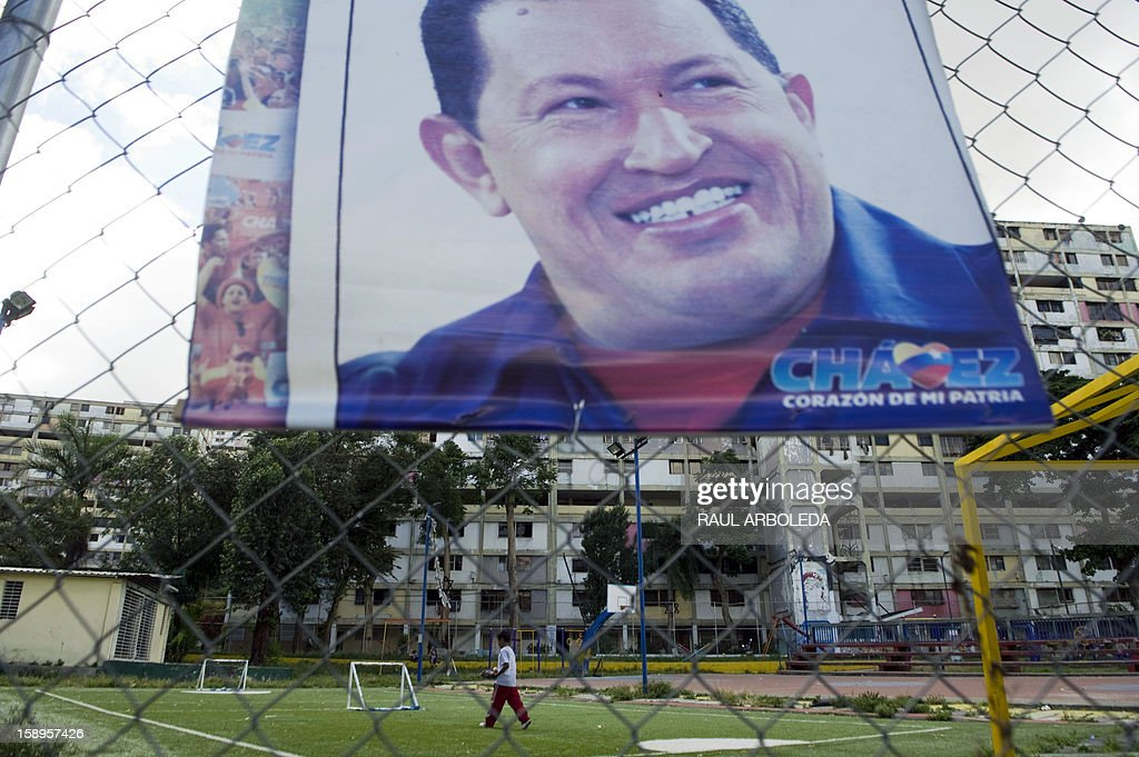 A boy walks near a poster with the image of Venezuelan President Hugo Chavez at the '23 de Enero' slum in Caracas on January 4, 2013. Hugo Chavez's top aides have gone on the offensive, accusing the opposition and media of waging a 'psychological war,' as Venezuela's cancer-stricken president battles a serious lung infection. The closing of ranks followed a high-level gathering of top Venezuelan officials in Havana with Chavez, amid growing demands to know whether he will be fit on January 10 to take the oath of office for another six-year-term. AFP PHOTO/Raul ARBOLEDA