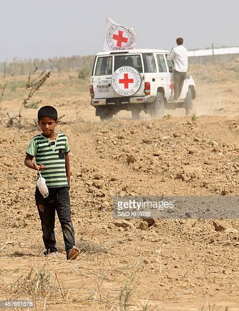 A boy walks near an International Committee of the Red Cross vehicle as the comittee assists Palestinian farmers to repair their fields that were...