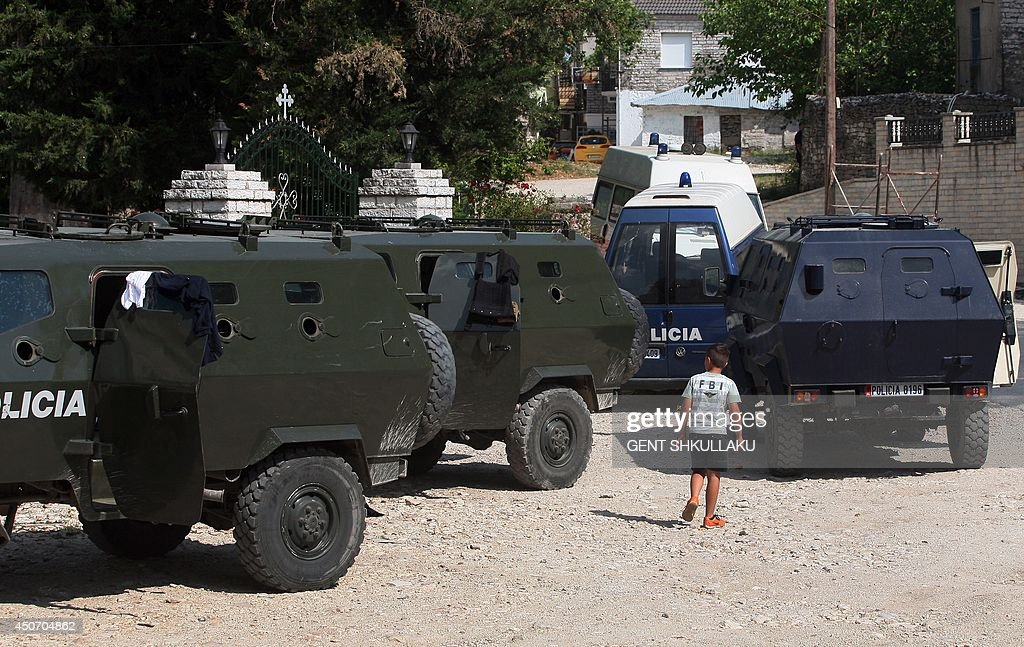 A boy walks next to armored police car as Albanian police perform checks on cars in the village of Lazarat south of the Albanian capital Tirana on...
