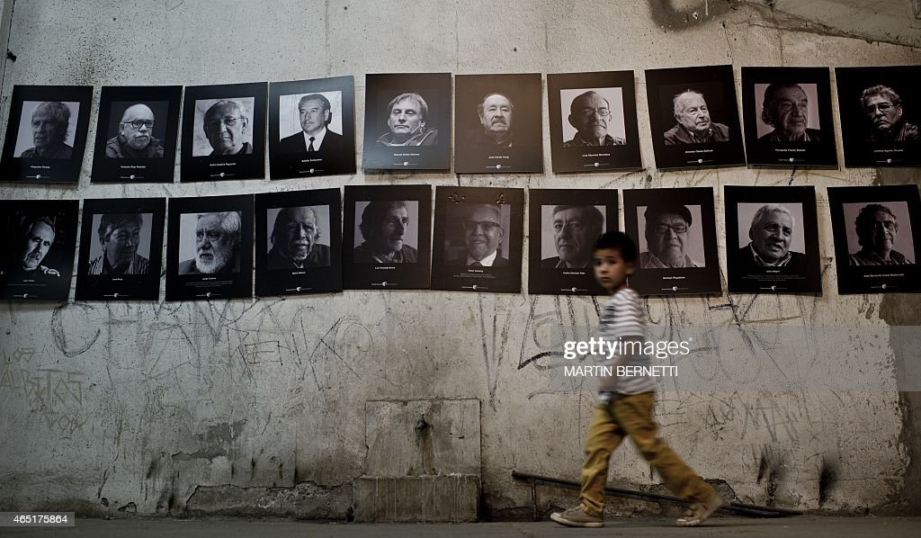 A boy walks next to pictures on display in a now gallery that once -during <a gi-track='captionPersonalityLinkClicked' href=/galleries/search?phrase=Augusto+Pinochet&family=editorial&specificpeople=93107 ng-click='$event.stopPropagation()'>Augusto Pinochet</a>'s dictatorship (1973-1990)- served as a jail for prisoners, in the National Stadium, in Santiago, on February 10, 2015. During the dictatorship the National Stadium was transformed into a detention and torture centre, which according to the International Red Cross housed over 20 thousand prisoners including men, women, children and 38 foreign citizens. AFP PHOTO/MARTIN BERNETTI