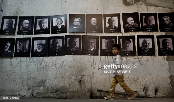 A boy walks next to pictures on display in a now gallery that once during Augusto Pinochet's dictatorship served as a jail for prisoners in the...
