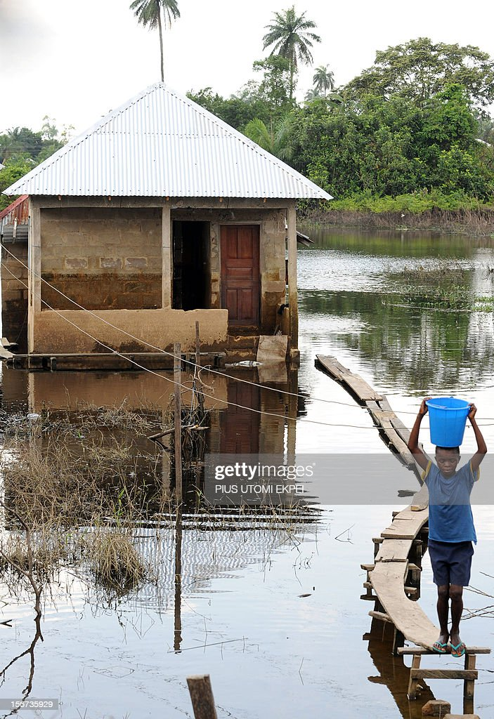 A boy walks on a footpath sitting on a flooded house in Yenagoa in the Bayelsa oil-rich Niger Delta region, on November 15, 2012. According to estimates from Nigerian authorities, surging waters this rainy season in Africa's most populous nation have killed at least 363 people and left another 2.1 million homeless. The flooding also slashed crude production by about 20 percent for a period in a country that is home to the continent's largest oil industry.