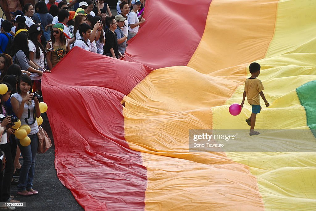 A boy walks on a rainbow flag during the Manila Gay Pride March on December 8, 2012 in Makati, Philippines. Although frowned upon by the mainstream Catholic church, Filipino LGBTs are slowly gaining ground as a vibrant and vocal movement as they prepare to field their very own political party in next year's midterm elections for the first time. The Ang Ladlad party (Coming Out party) is set to become Asia's very first lesbian gay bisexual transexual political party.