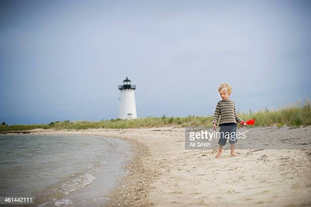 Boy walks on beach by lighthouse