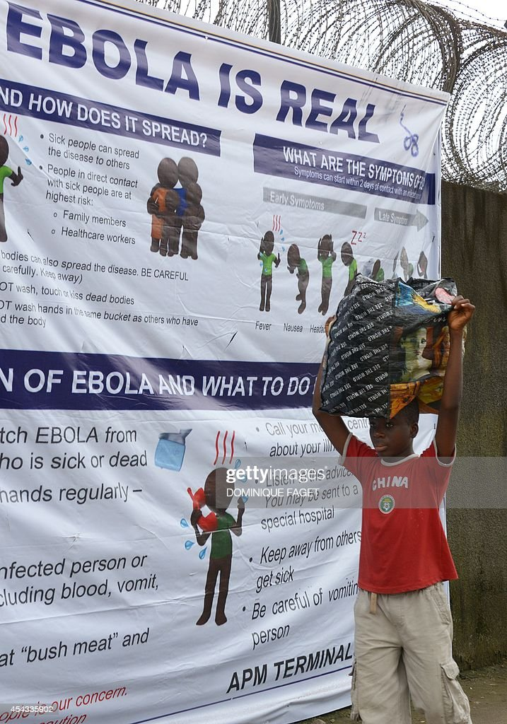A boy walks past a banner informing about the Ebola virus near the entrance of the port of Monrovia on August 29, 2014. The World Health Organization said yesterday that the number of Ebola cases was increasing rapidly and could exceed 20,000 before the virus is brought under control, as the death toll topped 1,500.