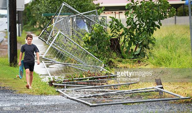 A boy walks past a fence brought down by Tropical Cyclone Marcia along the road into the northern Queensland town of Yeppoon on February 20 2015 Two...