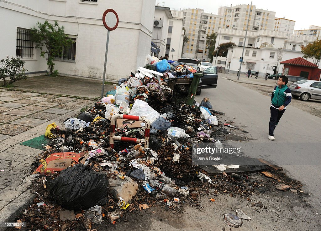 A boy walks past a pile of burnt uncollected garbage during the 20th day of the garbage collectors strike on November 21, 2012 in Jerez de la Frontera, Spain. The garbage collectors are protesting planned layoffs in the sector by the local town council.