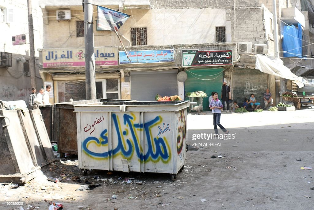 A boy walks past a rubbish container which is covered with a graffiti sprayed by Jumaa, an artist of the so-called 'Funny Media Activist' group, that aims to paint dumpsters all over Aleppo's rebel-held areas before the elections, on June 2, 2014 in the northern Syrian city of Aleppo. 'Cast your vote here,' Jumaa, sprayed on the metal containers in large, brightly coloured letters, transforming some of them into mock ballot-boxes. The graffiti means in Arabic 'The natural place of Bashar al-Assad'. AFP PHOTO / AMC/ ZEIN AL-RIFAI