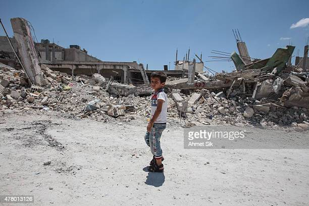 A boy walks past destroyed buildings in the center of the Syrian town of Kobane also known as Ain alArab Syria June 20 2015 Kurdish fighters with the...