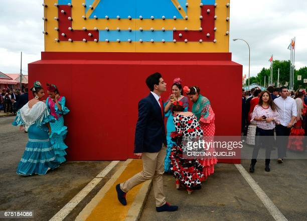A boy walks past girls wearing traditional Sevillian dresses during the 'Feria de Abril' in Sevilla on April 30 2017 The fair dates back to 1847 when...