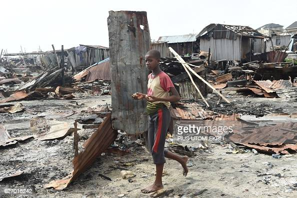 A boy walks past makeshift structures demolished by the authorities at Otodo Gbame waterfront fishing communities in Lagos on November 28 2016 Otodo...