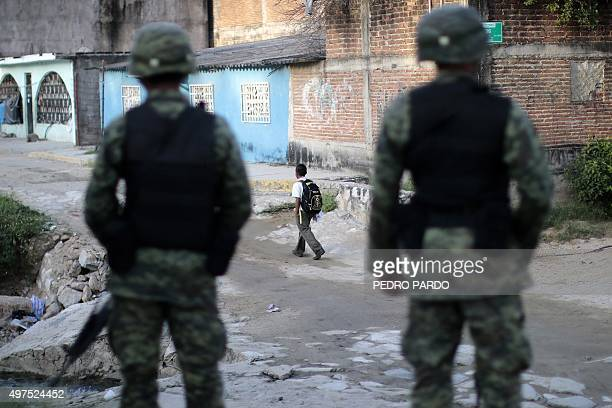 A boy walks past Mexican soldiers as they stand guard outside a school during a security operation following a strike of teachers due to criminal...