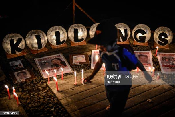 A boy walks past pictures of victims of extrajudicial killings during a vigil in Quezon city Metro Manila Philippines December 1 2017 On...