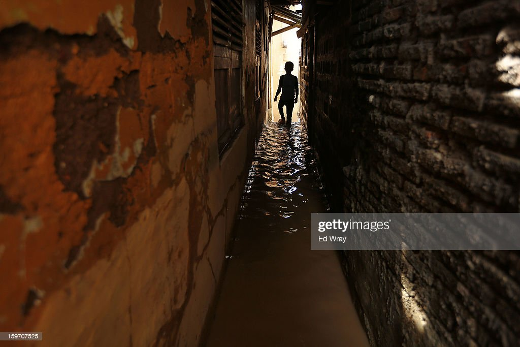 A boy walks thourgh his flooded neighborhood January 19, 2013 in Jakarta, Indonesia. Floodwaters receded today after three days of heavy flooding which left thousands of people's homes underwater. According to Indonesian police the death toll has reached 15.