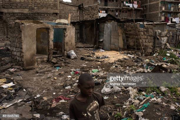 A boy walks through homes that were burned in unrest two days prior in the Mathare North neighborhood on August 14 2017 in Nairobi Kenya Nairobi...