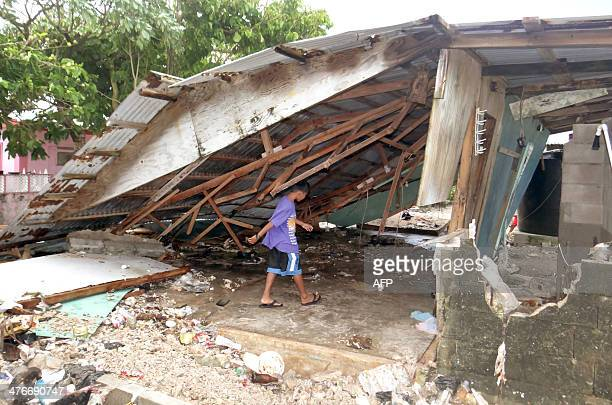 A boy walks under a damaged house at Majuro Atoll in the Marshall Islands on March 3 after a king tide coupled with storm surges causing widespread...