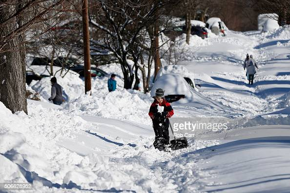 A boy walks up a snow covered street on January 24 2016 in Baltimore Maryland Millions of people are digging themselves out after a record snow storm...