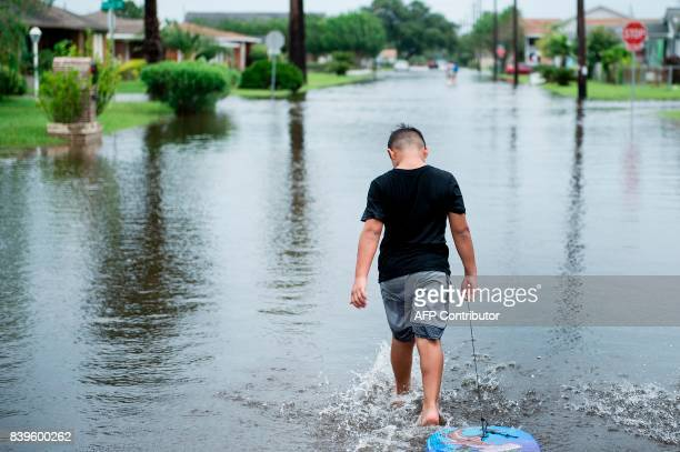 A boy walks with a bodyboard through a flooded street as the effects of Hurricane Harvey are seen August 26 2017 in Galveston Texas Hurricane Harvey...