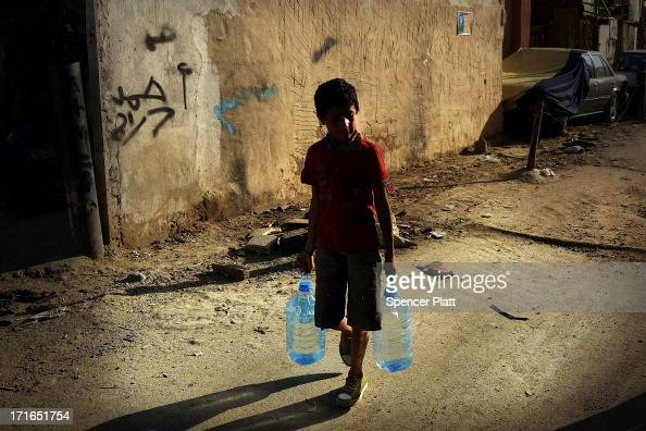 A boy walks with jugs of water in a poor neighborhood with a high concentration of Syrian refugees on June 27 2013 in Beirut Lebanon Currently the...