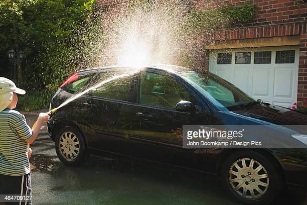 A Boy Washes A Car In The Driveway